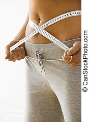 Woman on diet - Woman standing pulling measuring tape around...