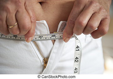 Woman on diet to loose weight - Woman with measure tape...