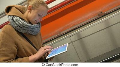 Woman on escalator using tablet computer