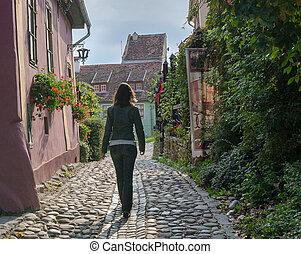 Woman on European cobblestone street - Woman walking on a...