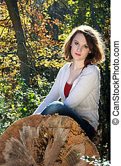Woman on fallen tree, autumn