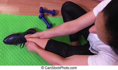 Woman on fitness mat massages painful ankle
