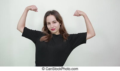 woman on gray background, strong girl shows muscles, bent ...