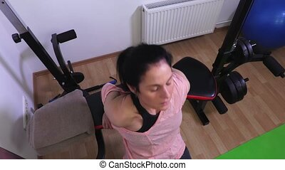 Woman on gym bench doing exercises for triceps