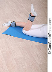 Woman on gym mat doing exercise