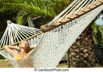 woman on hammock - woman relaxing on hammock with eyes...