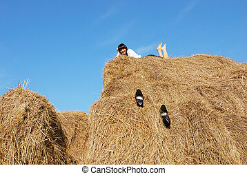 Woman on hay bale in summer field