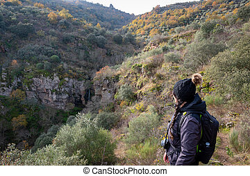 Woman on her back looking at a nature scene with a waterfall in the background