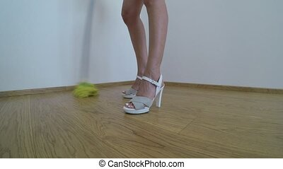 Woman on high heels washes the parquet floor with the yellow...