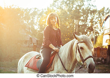 woman on horse at sunset