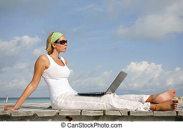 Woman in white looking at a laptop on a tropical boardwalk