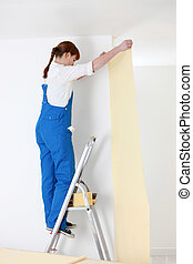 woman on ladder laying wallpaper