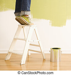Woman on ladder painting. - Legs of woman standing on tiptoe...