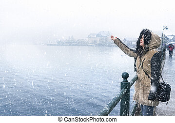 Winter destinations theme image with a woman standing on the Hallstatter lakeshore, catching snowflakes and enjoying the snowfall, in Hallstatt town, Austria.
