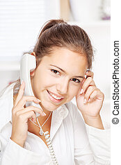 Woman on land line call, smiling at camera