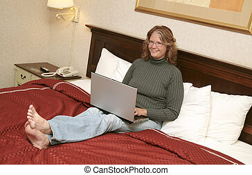 woman on laptop in bed