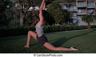 Woman on lawn makes a deflection back standing in attack on one leg.
