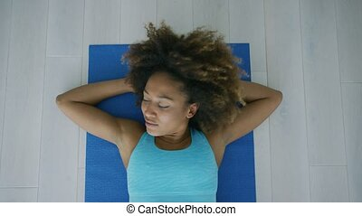 Woman on mat relaxing after workout - From above shot of...