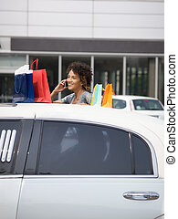woman getting out of limousine with shopping bags. Vertical shape, copy space