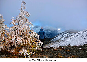 Woman on mountain top looking at scenic view of North Cascades in early winter.