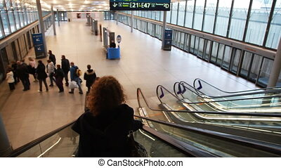 Woman on moving escalator - woman on moving escalator to...