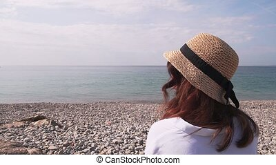 Woman on pebble beach looking at sea, rear view