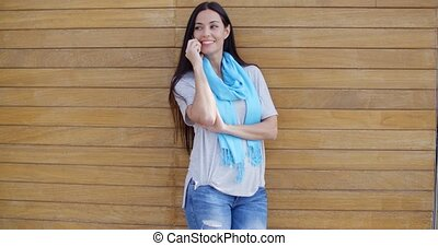 Woman on phone and leaning against wall - Attractive young...