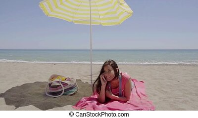 Woman on phone call at beach under umbrella