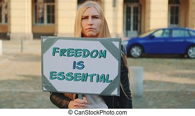 Woman on protest walk calling that freedom is essential by walking on the street with banner.
