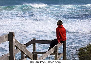Woman on railing at beach