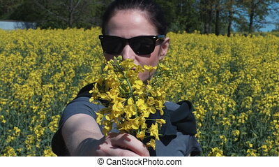 Woman on rapeseed field with yellow canola flowers.Pollen allergy concept
