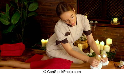 Woman on red towel have hot poultice massage in spa salon 4k...