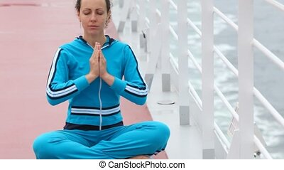 woman on rug sits in lotus pose on near hand-rail onboard ship
