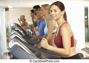woman in gym on machine exercising woman doing fitness