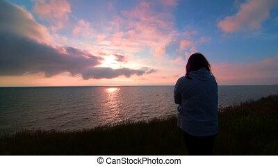 Woman on sea coast watching the sunset