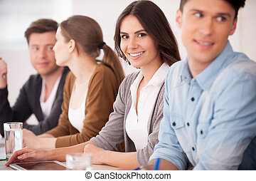 Woman on seminar. Group of young people sitting together at the table while beautiful woman looking at camera and smiling