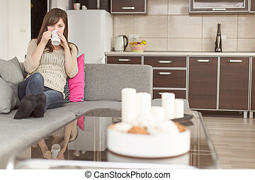 Woman on sofa having coffee