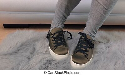 Woman on sofa lace up sneakers