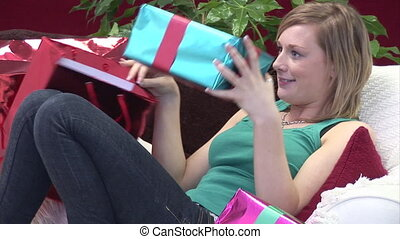 Woman on Sofa with Christmas Presents - Christmas Stock...