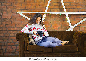 Woman on sofa with photo camera