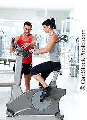 woman on stationary bicycle with personal trainer at fitness...