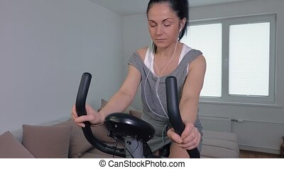 Woman on stationary exercise bicycle