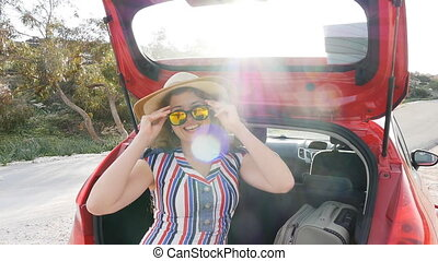 Woman on summer travel vacation sitting in a car trunk