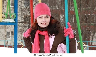 woman on swings against the background of the playground