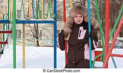 Woman on swings, looks and smiling