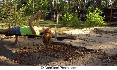 Woman on swings with smartphone making selfy - Chilling...