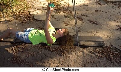 Woman on swings with smartphone