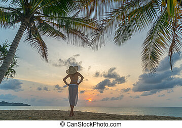 Woman on the beach at sunset under the coconut trees