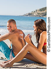 Woman on the beach drawing heart pattern with sun cream on her boyfriends back