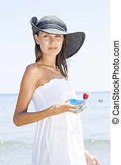 Woman on the beach drinking a cocktail